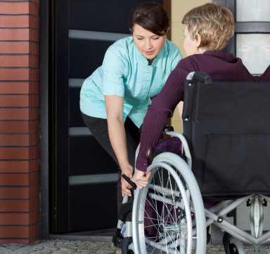 caregiver assisting her patient in wheelchair